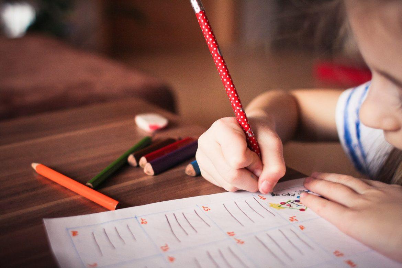 bambina che scrive con la matita