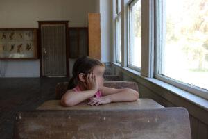 bambino scuola solo che guarda alla finestra